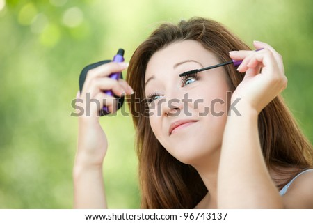Portrait of young pretty woman imposes shadow and looking in mirror at summer green park - stock photo