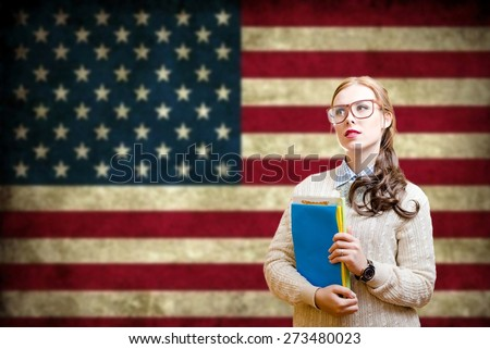 Portrait of young pretty woman in glasses holding books with the USA flag on the background. - stock photo
