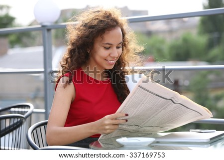 Portrait of young pretty woman in red dress reading newspaper at summer terrace - stock photo