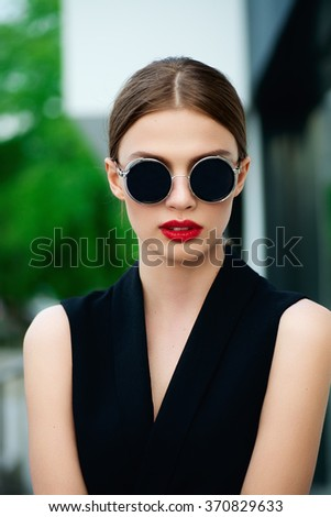 Portrait of young pretty woman in summer sunny day on street - stock photo