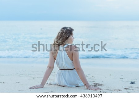 Portrait of young pretty woman sitting on the Beach.Woman sitting on the beach turned wistfully looking at the sky.girl on the beach watching the sunset.Bali.Indonesia Ho;iday - stock photo