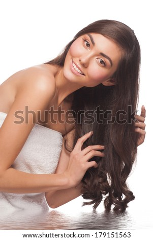 Portrait of young pretty woman washing her long healthy hair in water, against white background - stock photo