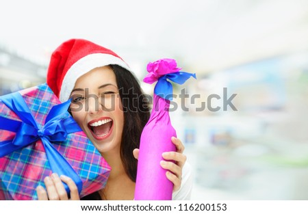 Portrait of young pretty woman wearing Santa Claus helper hat standing inside shopping mall smiling and holding christmas gifts - stock photo