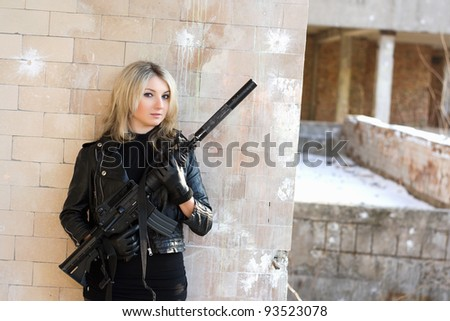Portrait of young pretty woman with a gun - stock photo