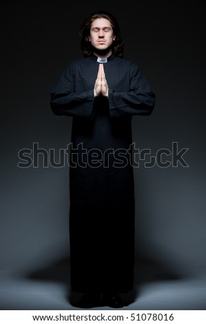 portrait of young priest is praying against dark background - stock photo