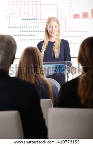 Portrait of young professional woman giving speech at business seminar. - stock photo