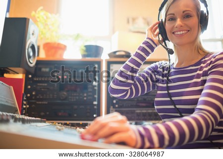 Portrait of young radio host using sound mixer in studio - stock photo