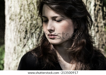 Portrait of young, sad woman in black - stock photo