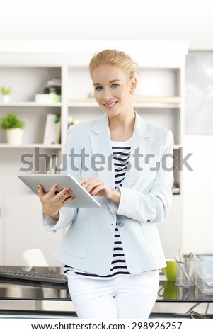 Portrait of young sales assistant standing at office and holding digital tablet in her hands, touching the screen while looking at camera and smiling. Attractive businesswoman wearing casual clothing. - stock photo