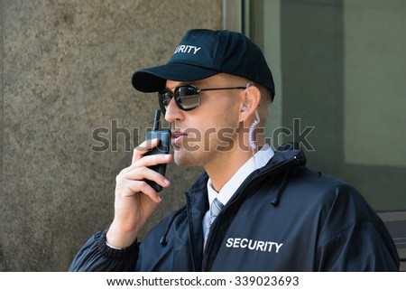 Portrait Of Young Security Guard Using Walkie-talkie Radio - stock photo