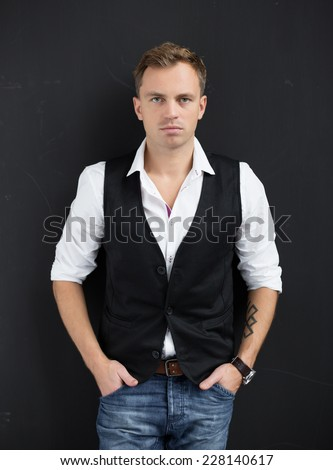 Portrait of young serious man standing against black background - stock photo