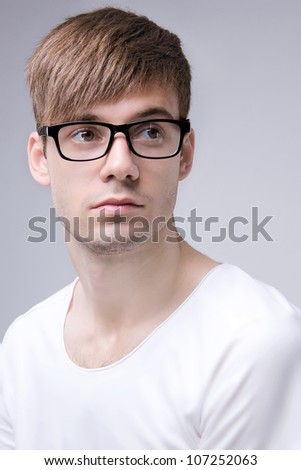 Portrait of young serious man with glasses  in white shirt on a grey background - stock photo