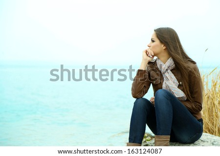Portrait of young serious woman near river - stock photo