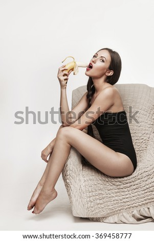Portrait of young sexy brunette sitting in armchair and eating  banana fruit. Beautiful woman with long legs dressed in black bodysuit posing in studio.  - stock photo