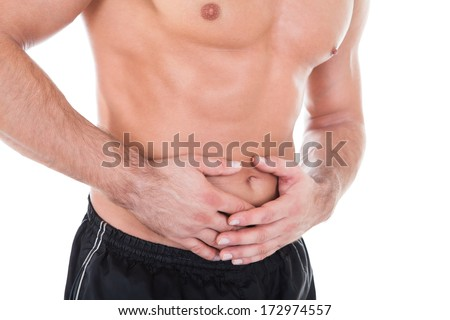 Portrait Of Young Shirtless Man Having Stomachache - stock photo