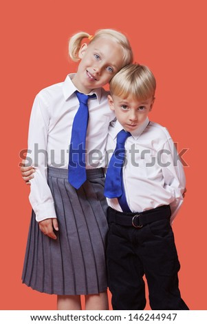 Portrait of young siblings in school uniform with arm around over orange background - stock photo