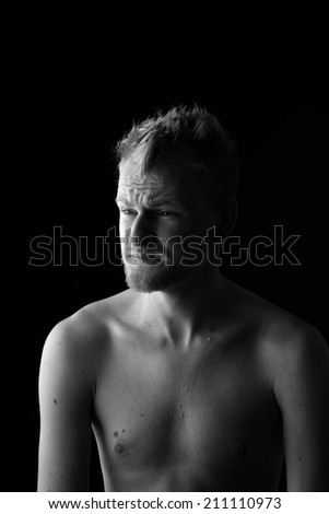 Portrait of young skeptical man frowning his forehead on black background - stock photo