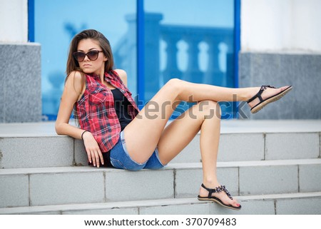 Portrait Of Young Smiling Beautiful Woman. Close-up portrait of a fresh and beautiful young fashion model posing outdoor in sunny weather. woman portrait. smiling girl in city street - stock photo