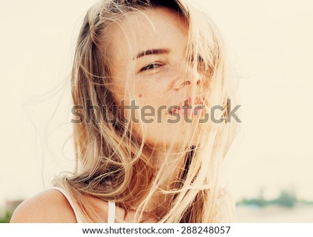 Portrait Of Young Smiling Beautiful Woman with Hair Blowing in the Wind. Warm Color Toned - stock photo