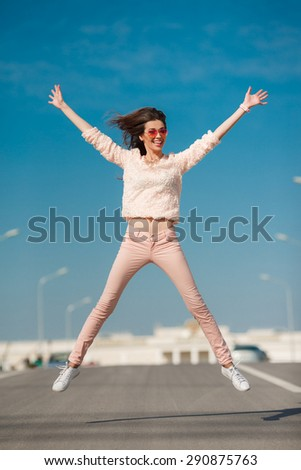 Portrait Of Young Smiling Beautiful Woman. Young woman having fun outdoors on road and sky background. Beautiful smiling young woman jumping, against background of blue sky. - stock photo