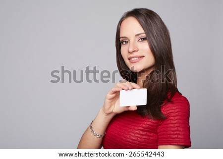 Portrait of young smiling business woman holding credit card isolated on gray - stock photo