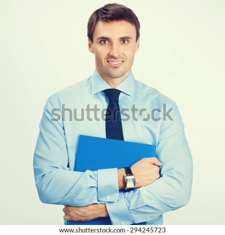 Portrait of young smiling businessman in blue confident business wear with folder - stock photo