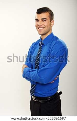 Portrait of young smiling businessman in blue shirt and tie - stock photo