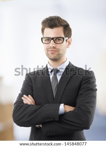 Portrait of young smiling businessman in office - stock photo