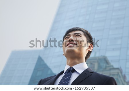 Portrait of young smiling businessman outside glass building - stock photo