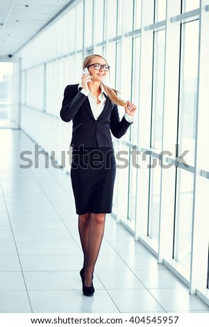 Portrait of young smiling businesswoman talking on the phone in business center. Full-length.  - stock photo