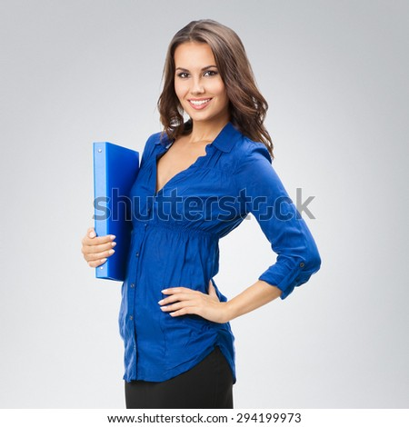 Portrait of young smiling businesswoman with blue folder, posing at studio against grey background - stock photo