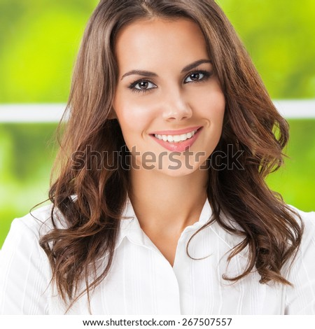 Portrait of young smiling cheerful businesswoman at office - stock photo