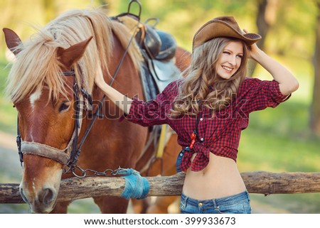 Portrait of young smiling cowgirl and horse outdoors - stock photo