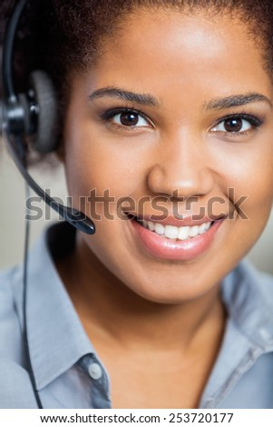 Portrait of young smiling female customer service representative wearing headset in office - stock photo