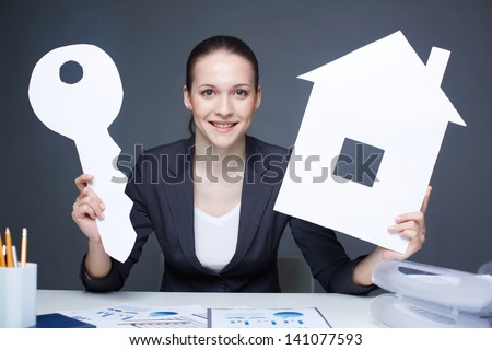 Portrait of young smiling female holding paper house and key and looking at camera - stock photo