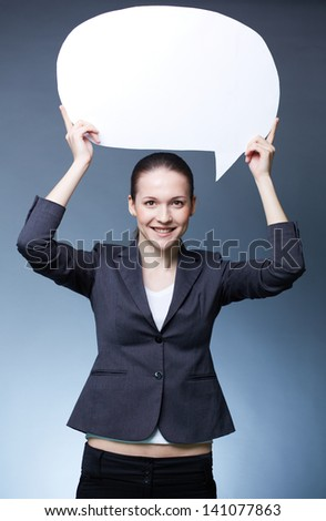 Portrait of young smiling female holding paper speech bubble over her head - stock photo