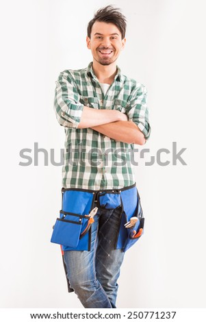 Portrait of young, smiling man with tools for home repair. - stock photo