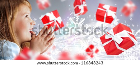 Portrait of young smiling praying girl looking up against silver fairy snowstorm background. Red gift boxes are flying around - stock photo