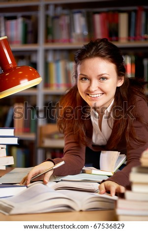 Portrait of young smiling teacher looking at camera in college library - stock photo