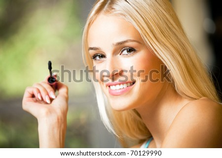 Portrait of young smiling woman applying mascara - stock photo