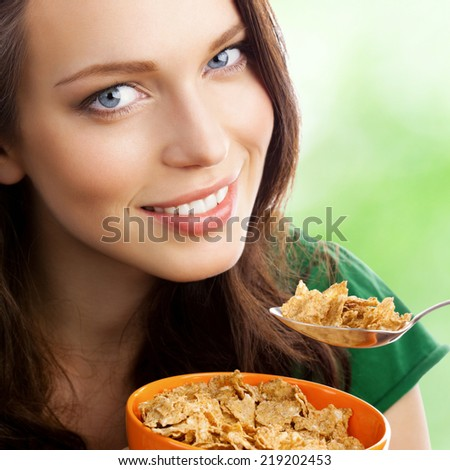 Portrait of young smiling woman eating muesli or cornflakes, outdoor - stock photo