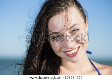 Portrait of young smiling woman posing at the seaside - stock photo