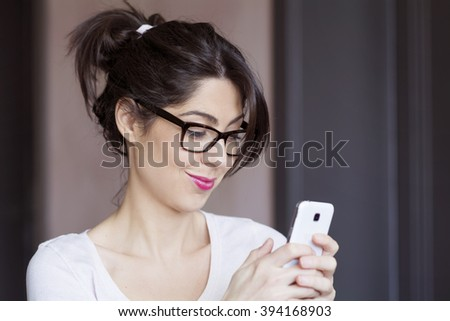 Portrait of young smiling woman receiving funny message - stock photo