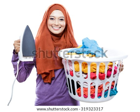 portrait of young smiling woman wearing hijab holding iron and carrying laundry basket isolated on white - stock photo