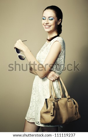 Portrait of young smiling woman with a leather bag. Fashion photo - stock photo