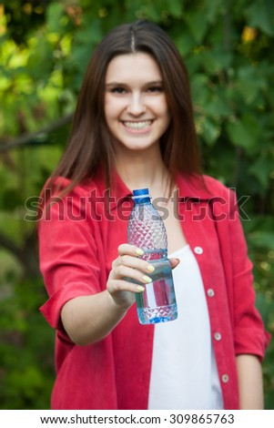 Portrait of young smiling woman with bottle of water, outdoor.A close up portrait of a young woman with bottle of water - stock photo