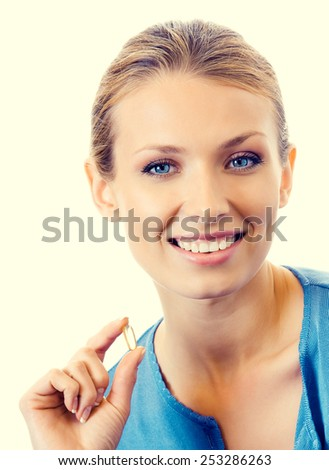 Portrait of young smiling woman with Omega 3 fish oil capsules - stock photo