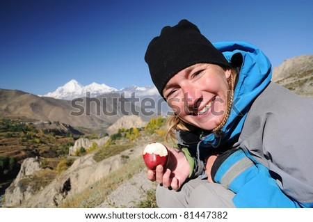 Portrait of young smiling woman with red apple, Dhaulagiri peak in backgroung, Annapurna circuit trek, Nepal - stock photo