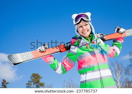 portrait of young smiling woman with ski on winter holiday in mountains - stock photo