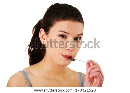 Portrait of young smiling woman with spoon in her mouth (pleasure from eating), isolated on white  - stock photo